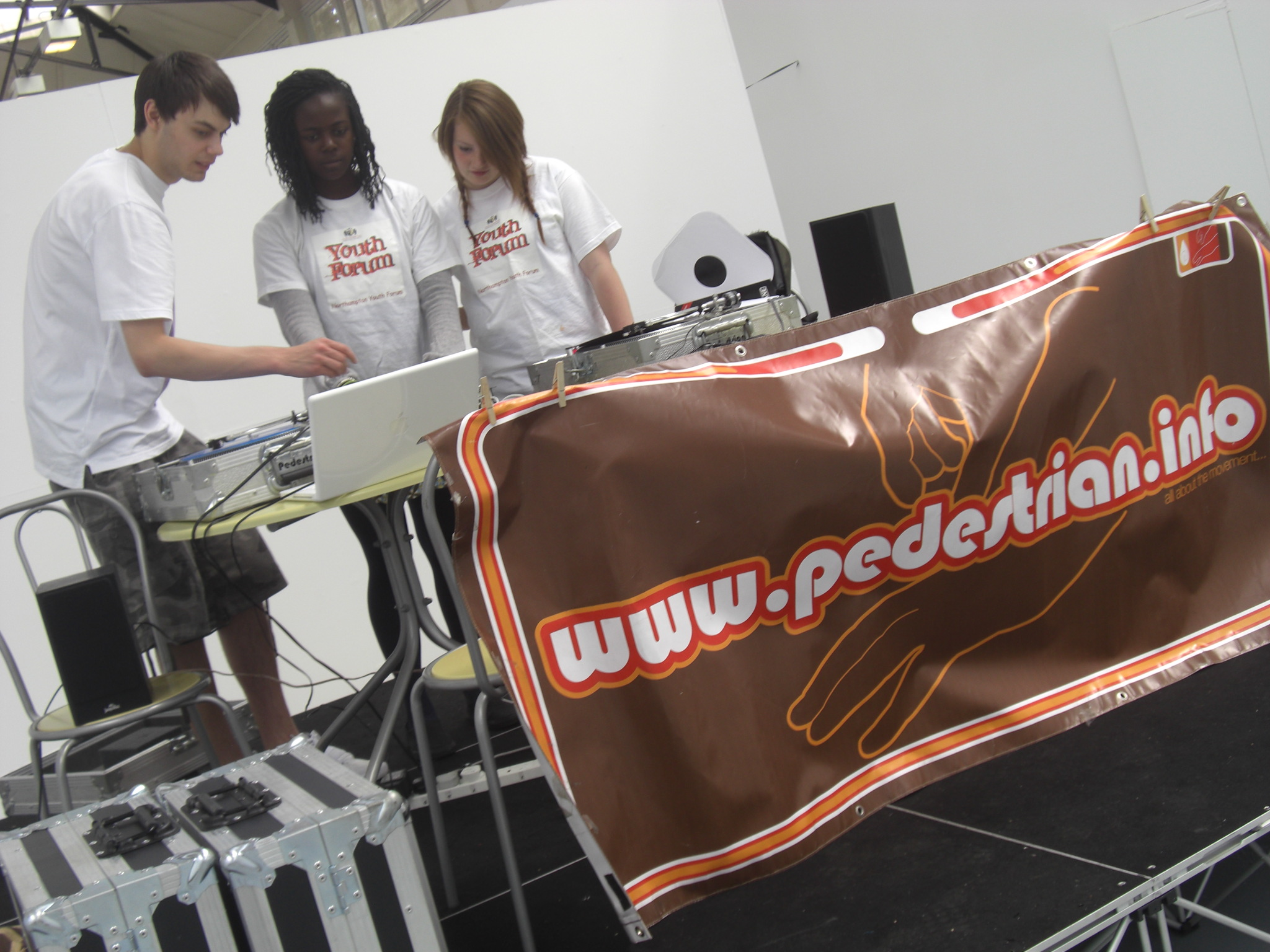 2 children learning how to Dj. Pedestrian website banner hangs from the table in front of them.