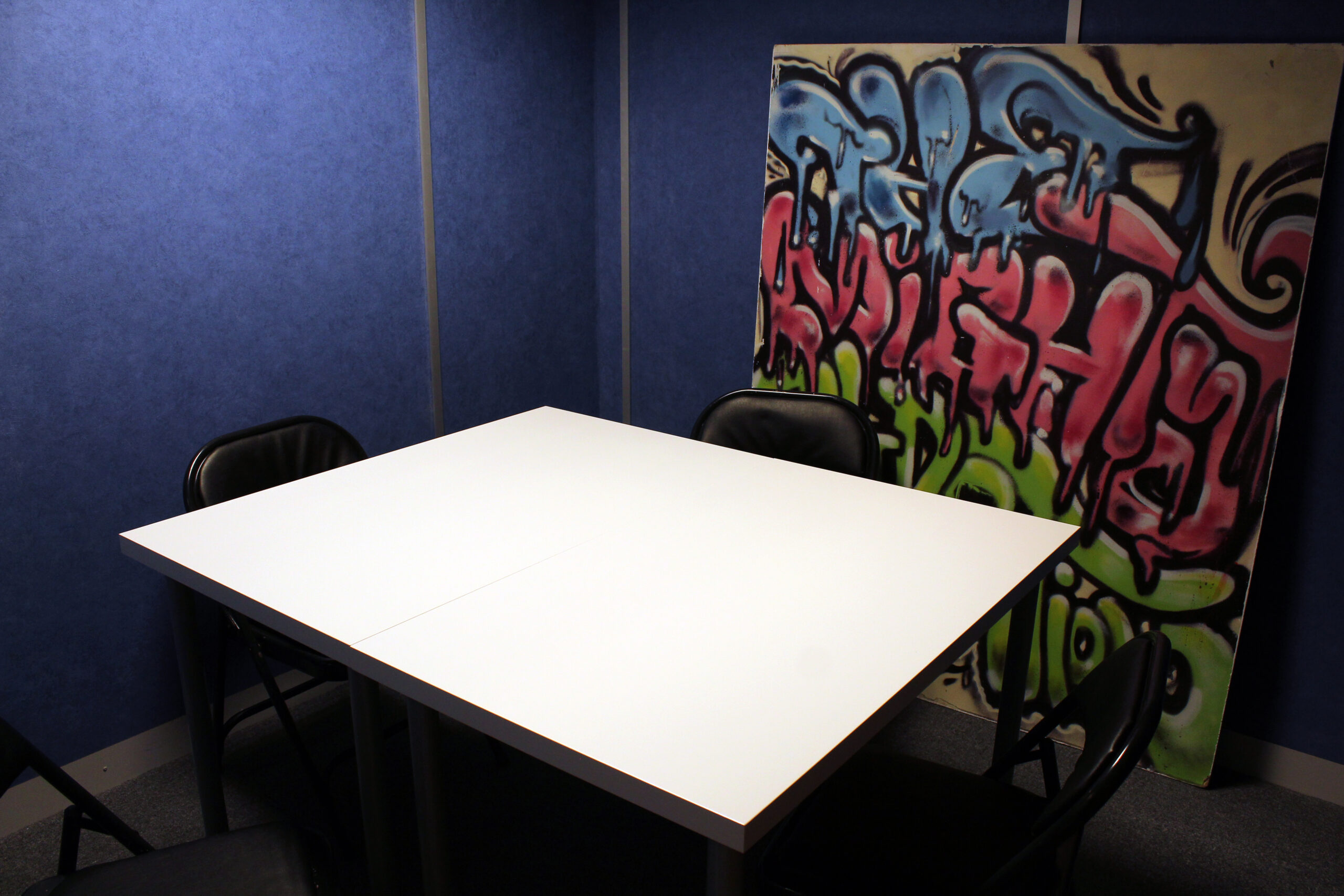 Photo of Meeting room with Blue walls, large graffiti print & white table / black chairs