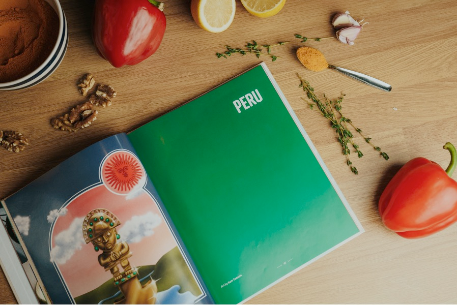 Image open cookbook with tomatoes, pepper, lemon & thyme spread around on a wooden surface. Cookbook is open with an emerald green page = white text: PERU