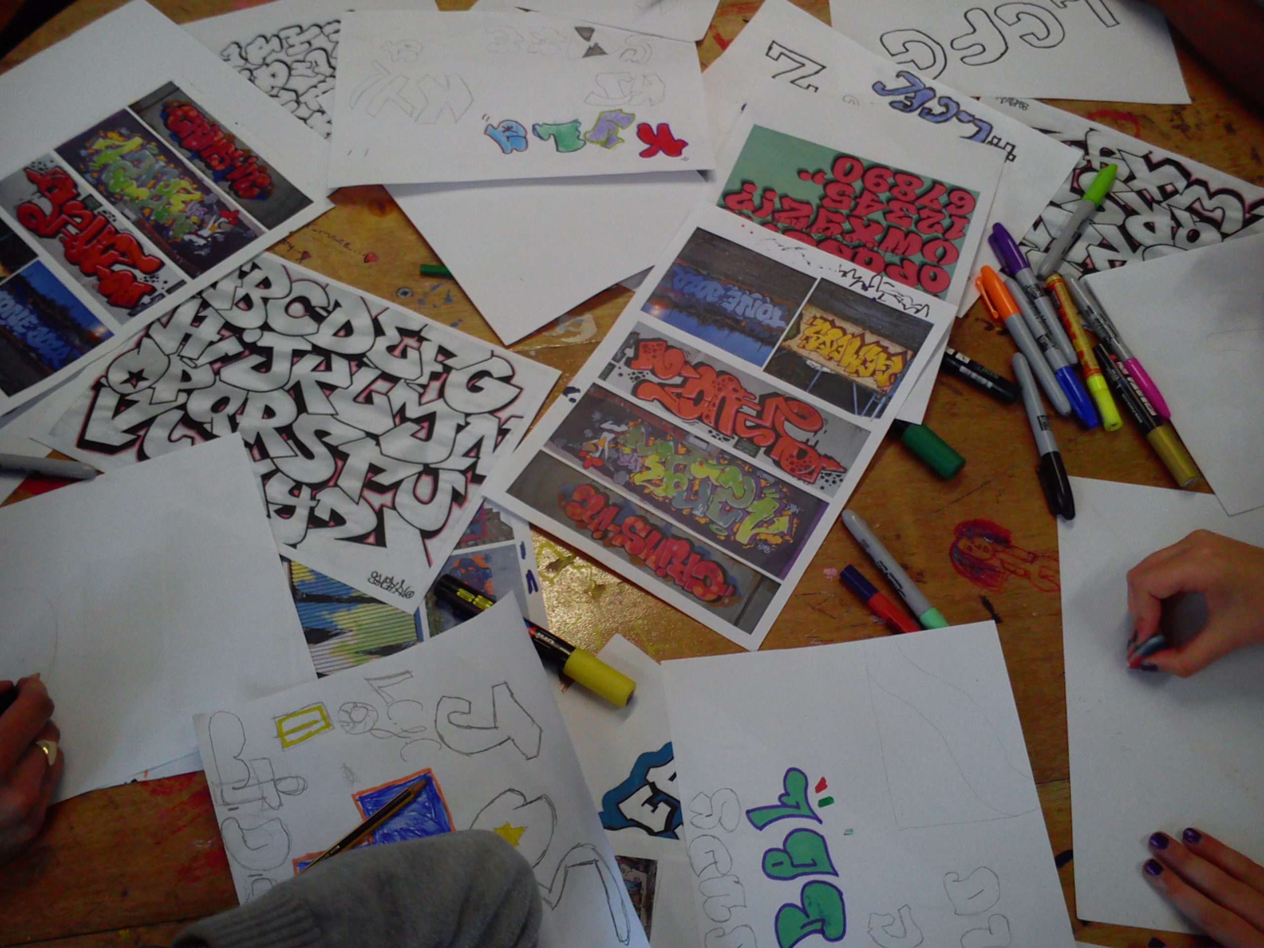 A wooden table with examples of colourful graffiti tags, Posca pens & the hands of young people creating their own tags