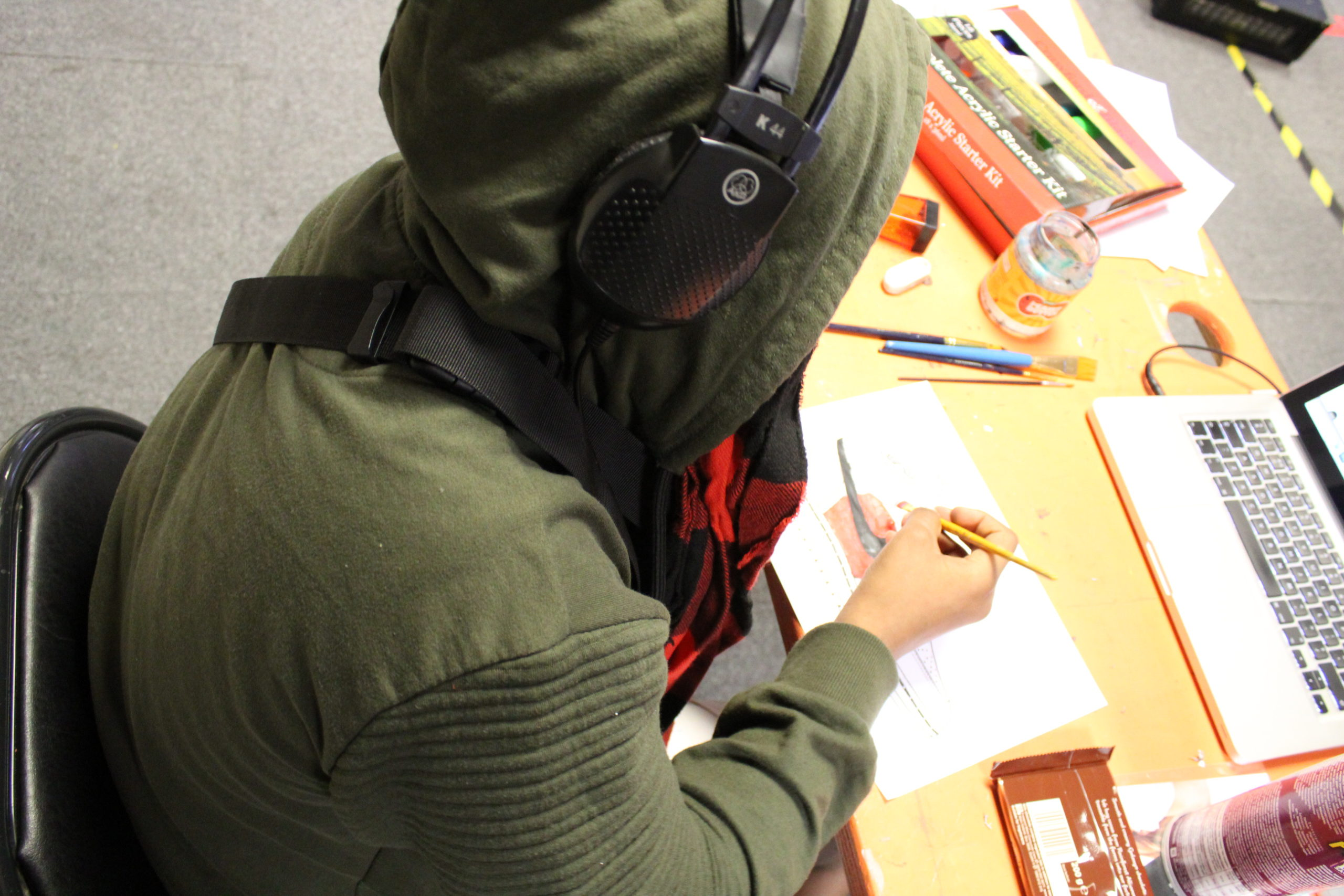 photo of young person in khaki hooded top with black headphones over the top drawing in front of a laptop