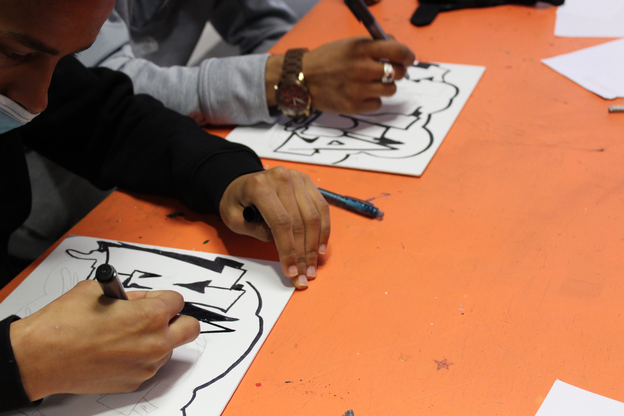 photo of two young people drawing graffiti tags with Posca pens
