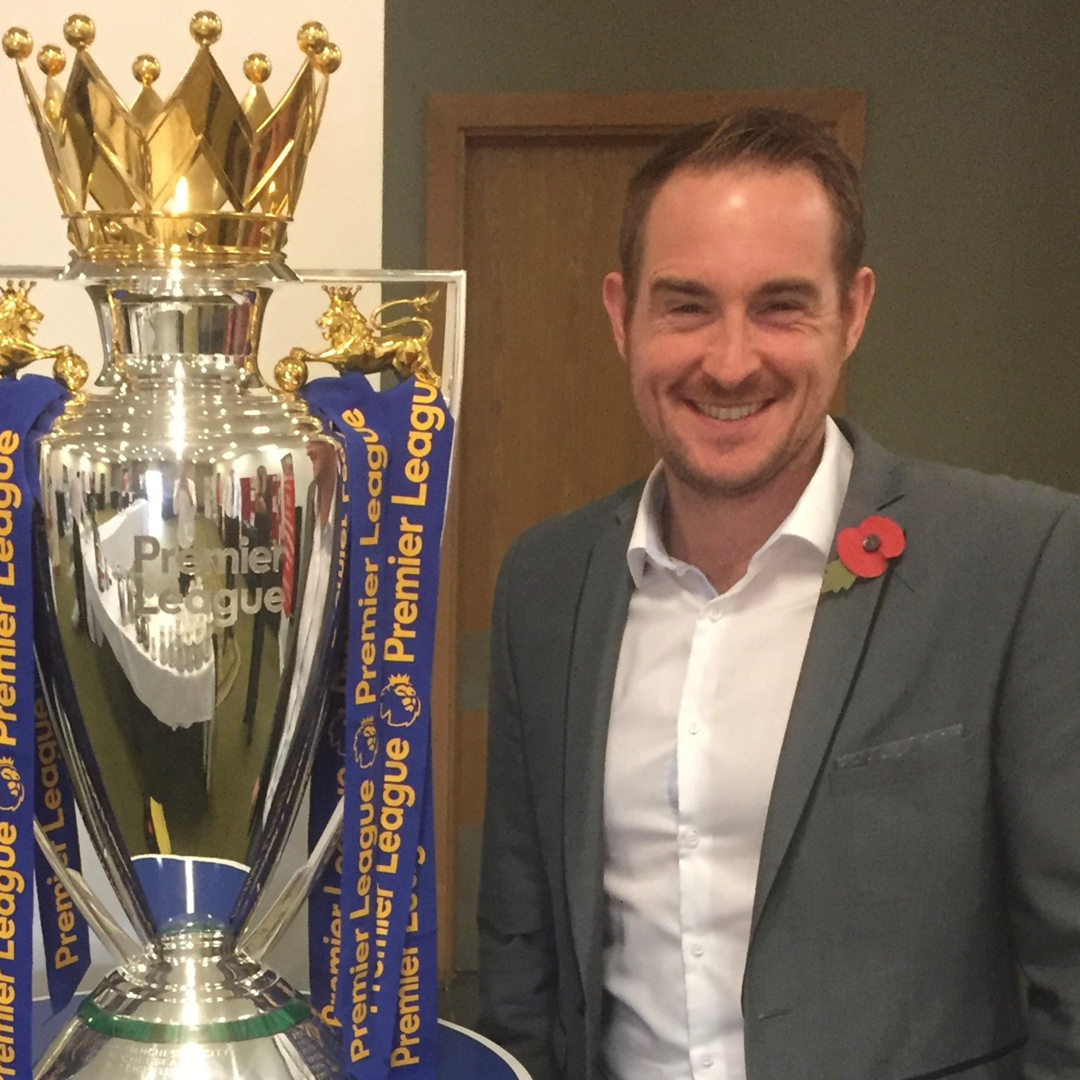 Dan wearing a suit smiling whilst standing next to the FA cup