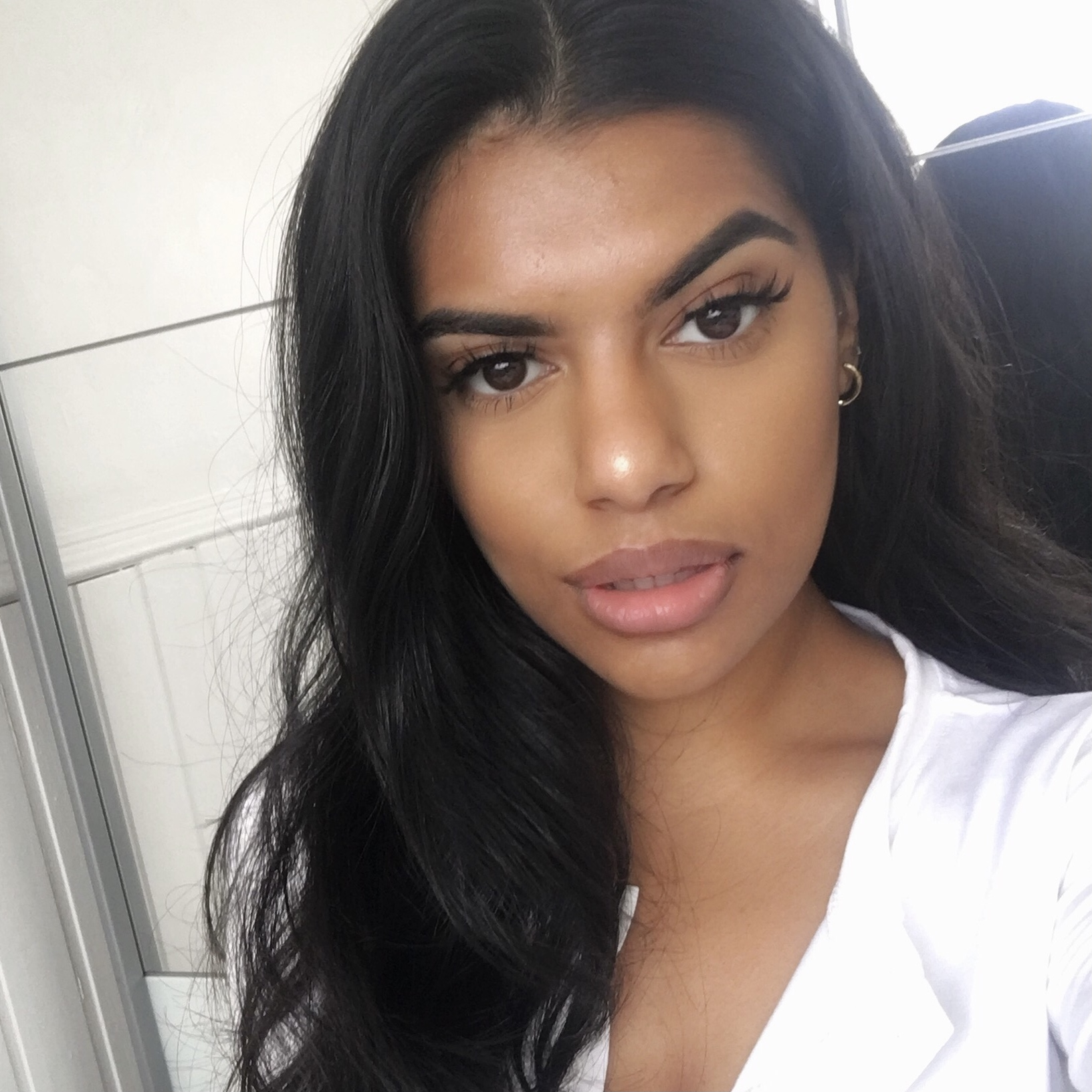 Dalisha looking directly into the camera wearing a white top