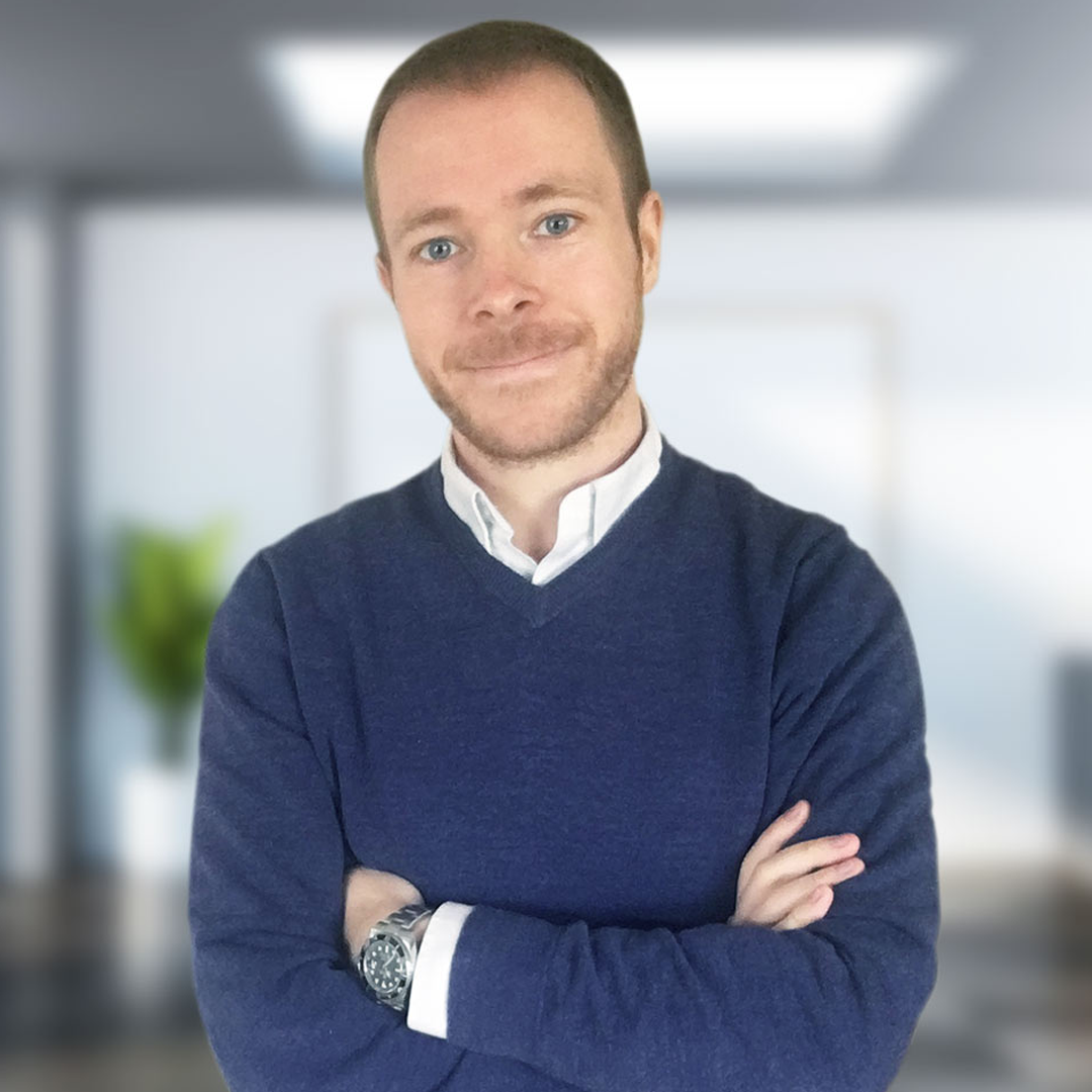 Joe standing with arms folded wearing a blue jumper over a white shirt