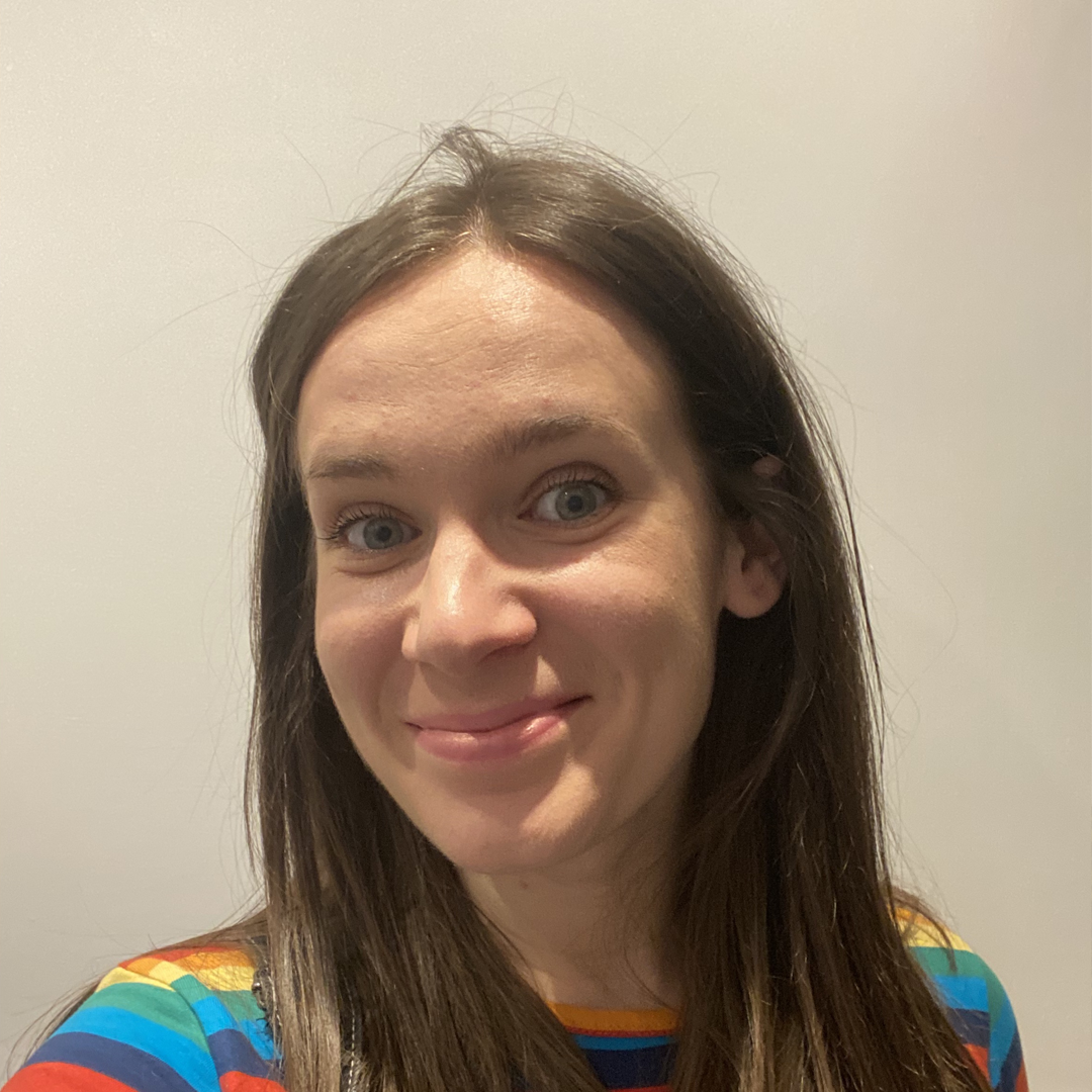 Jenny smiling with her hair down wearing a rainbow stripe top