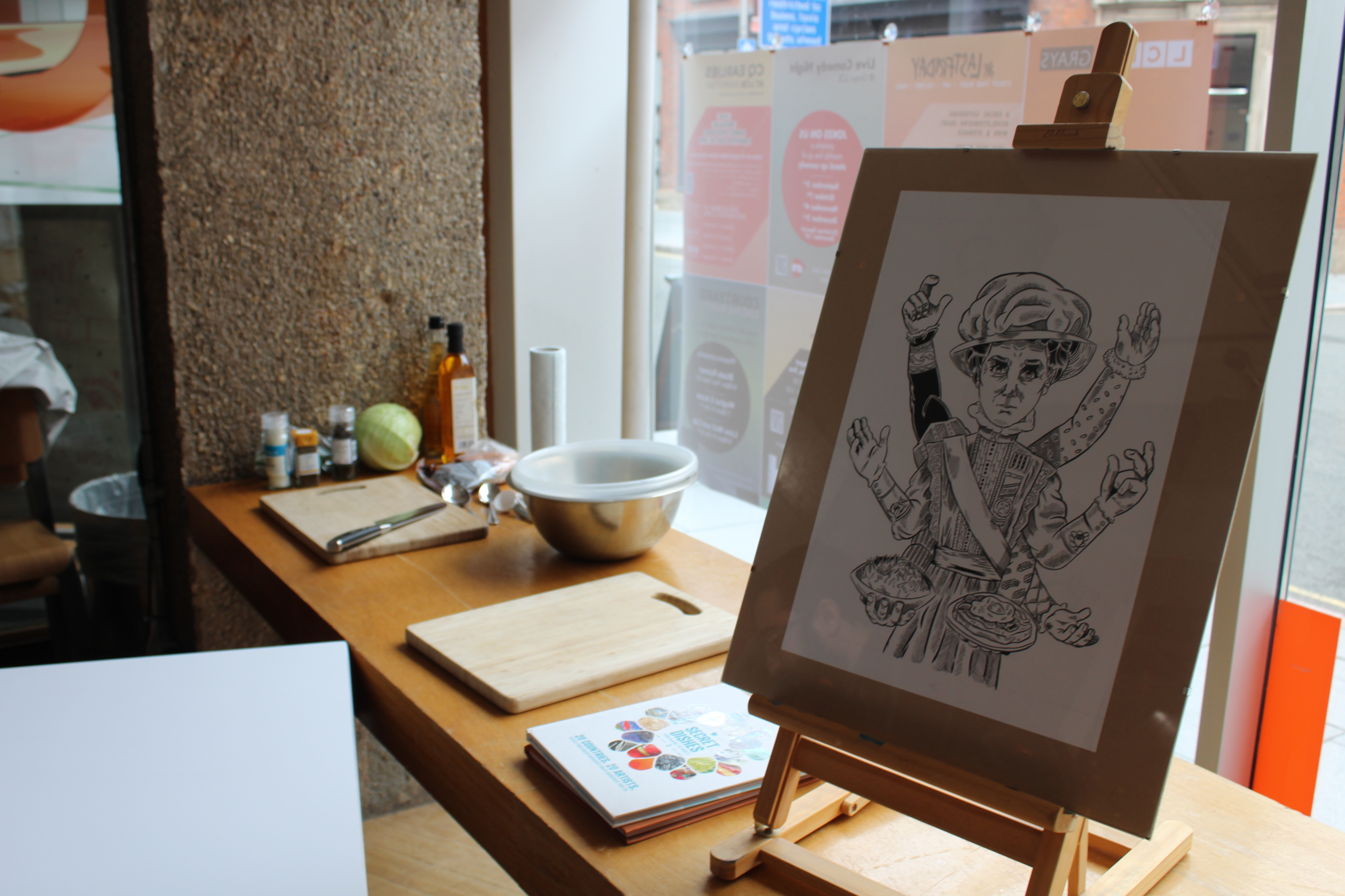 Photograph of original artwork for Secret Dishes from around the world 3.  A black & white illustration of Alice Hawkins - Sufferagette.  The illustration is in a frameless frame on a wooden easle in the window of LCB Depot.  In the background you can see ingredients for a recipe.